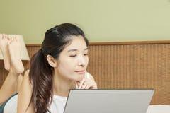 愉快的年轻亚裔妇女与膝上型计算机一起使用在卧室 库存图片