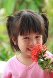 愉快的年轻亚洲女孩气味花 免版税图库摄影