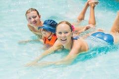 愉快的年轻人两名妇女和男孩演奏和有好时光在水乐趣公园水池,在一夏天热的天 库存照片