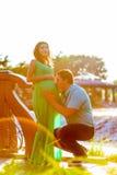 愉快的年轻人亲吻他怀孕的妻子腹部 库存照片