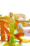 愉快的年轻人亲吻他怀孕的妻子腹部 免版税库存图片