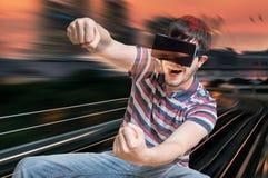 愉快的年轻人使用赛跑在3D虚拟现实模拟器的计算机游戏 库存照片