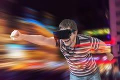 愉快的年轻人使用赛跑在3D虚拟现实模拟器的计算机游戏 免版税图库摄影
