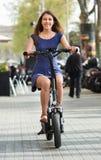 愉快的年轻人和妇女有electrkc自行车的 库存图片