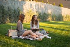 愉快的年轻人坐户外在公园文字笔记的两名妇女 库存照片