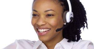 愉快的黑人女实业家谈话与耳机 免版税库存图片