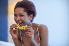 年轻愉快的黑人妇女在床和吃上坐橙色切片 免版税库存照片