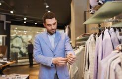 愉快的年轻人尝试的夹克在服装店 免版税库存图片