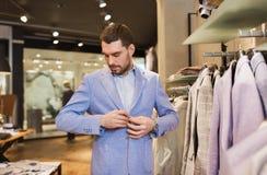 愉快的年轻人尝试的夹克在服装店 库存照片