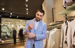 愉快的年轻人尝试的夹克在服装店 免版税库存照片