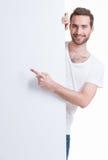 愉快的年轻人指向在一副空白的横幅的手指 免版税图库摄影