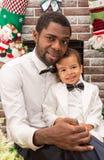 愉快的黑人父亲和拥抱由壁炉的男婴 圣诞节 免版税库存照片