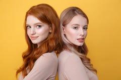 愉快的年轻人站立在黄色背景的两个夫人 库存照片