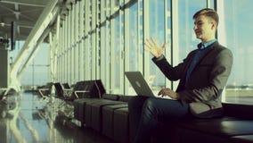 愉快的年轻人键入某事在他的膝上型计算机,当坐在机场时 股票录像