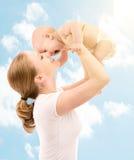 愉快的系列。 亲吻天空的母亲婴孩 免版税库存图片