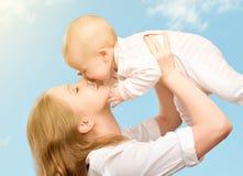 愉快的系列。 亲吻天空的母亲婴孩 免版税库存照片