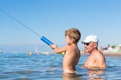 愉快的系列 使用在海的微笑的祖父和孙子 正面人的情感,感觉, 免版税库存图片