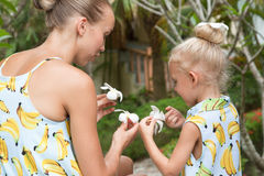 愉快的系列 年轻坐在有花的一个热带庭院里的母亲和女儿在他们的手上 图库摄影
