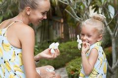 愉快的系列 年轻坐在有花的一个热带庭院里的母亲和女儿在他们的手上 库存照片