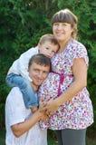 愉快的系列 有她的丈夫和儿子的怀孕的母亲在公园 免版税库存照片