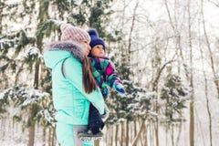 愉快的系列 母亲和儿童女孩在一个冬天走本质上 免版税库存照片