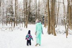 愉快的系列 母亲和儿童女孩在一个冬天走本质上 免版税库存图片
