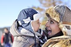 愉快的系列 年轻母亲在有她的甜婴孩的一个冬天公园 库存照片