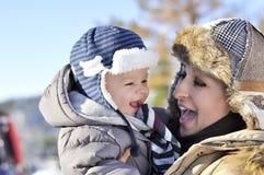 愉快的系列 年轻母亲在有她的甜婴孩的一个冬天公园 图库摄影
