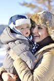 愉快的系列 年轻母亲在有她的甜婴孩的一个冬天公园 免版税图库摄影