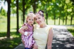 愉快的系列 照顾和女儿神色在照相机,微笑, emb 免版税图库摄影