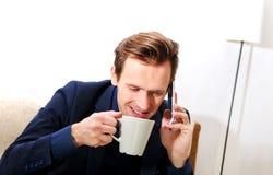 愉快的年轻商人谈话通过电话和饮用的咖啡或者茶 免版税库存图片