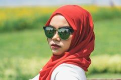 愉快的年轻回教妇女红色hijab画象  免版税库存照片