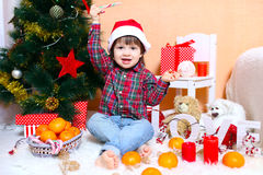 愉快的2年圣诞老人帽子的男孩在圣诞树附近坐 免版税库存照片