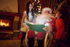 愉快的从圣诞老人的女孩听的不可思议的童话 免版税库存图片