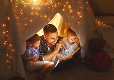 愉快的读在帐篷的家庭父亲和孩子一本书在hom 免版税库存图片
