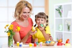 愉快的绘复活节彩蛋的母亲和孩子 库存图片
