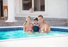 愉快的年轻夫妇和女儿游泳池的在豪华别墅附近 免版税库存照片