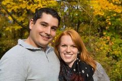 愉快的年轻夫妇在做步行的秋天在新鲜空气 免版税库存图片
