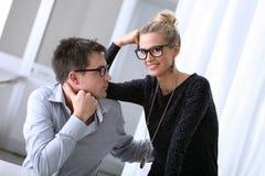 愉快的年轻夫妇在办公室 库存照片