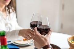 愉快的年轻夫妇在家吃的和饮用的酒和敬酒用酒 免版税库存图片