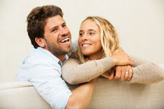 愉快的年轻夫妇在家在沙发 免版税库存图片