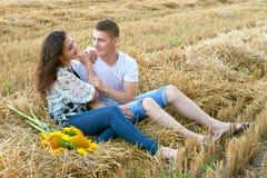愉快的年轻夫妇在小麦领域坐晚上,浪漫人概念,美好的风景,夏季 免版税库存照片