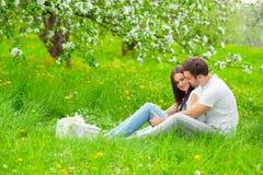 愉快的年轻夫妇在庭院用苹果开花 免版税图库摄影