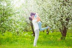 愉快的年轻夫妇在庭院用苹果开花 免版税库存图片