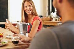 愉快的年轻夫妇在食用的厨房里早餐 库存照片