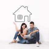 愉快的年轻夫妇坐地板使用购物和娱乐的一种片剂 格式 图画房子作为背景 图库摄影
