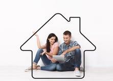 愉快的年轻夫妇坐地板使用购物和娱乐的一种片剂 格式 图画房子作为背景 免版税库存图片