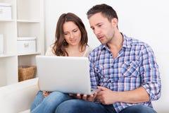 愉快的年轻夫妇坐长沙发使用膝上型计算机 免版税图库摄影