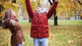 愉快的年轻夫妇投掷的秋叶在公园 股票录像