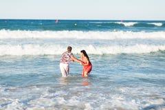 愉快的年轻夫妇有乐趣、男人和妇女在海滩的海 免版税库存照片